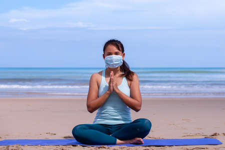 people, fitness, sport and healthy lifestyle concept - young asian girl making maditation in medical mask on tropical beach