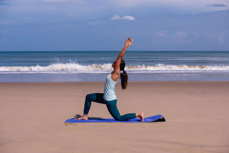 people, fitness, sport and healthy lifestyle concept - young asian woman making warrior yoga poses on tropical beach with blue sky background