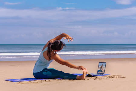 people, fitness, sport and healthy lifestyle concept - young asian woman watching in laptop and making yoga on tropical beach with blue sky background. Standard-Bild