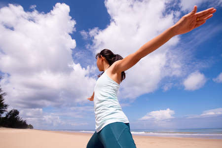 people, fitness, sport and healthy lifestyle concept - young asian woman making warrior yoga poses on tropical beach with blue sky background. Standard-Bild