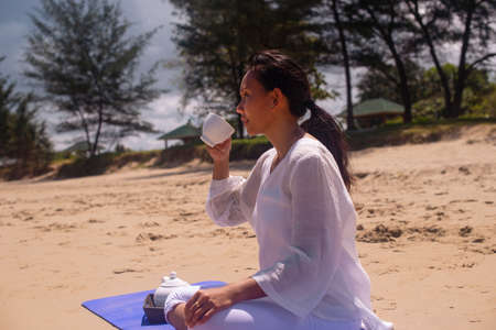 people and leisure concept- back view of woman meditating and drinking tea on the tropical beach