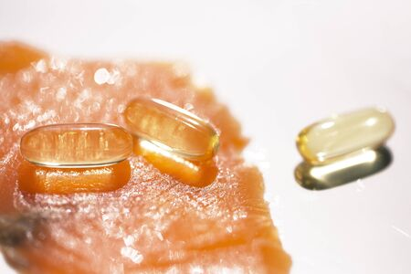 Useful Fish Oil Capsules. Close-up of salmon fillet and pills layout.