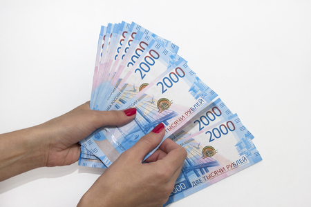 a womans hand holds paper money. Russian rouble