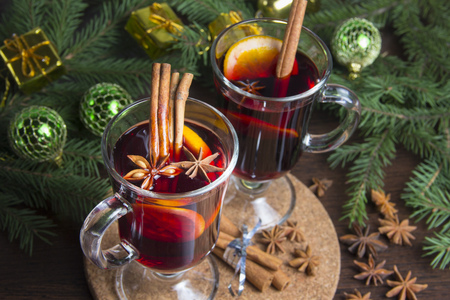 Christmas mulled wine with cinnamon and orange. On the table are spruce twigs and toys