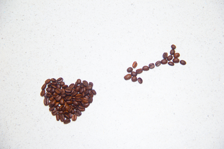 Spilled coffee beans. Coffee in the form of hearts.