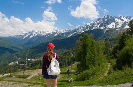 Le touriste en pleine croissance se tient sur le rivage près de la rivière de montagne et de la forêt autour