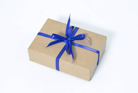 Gift box with blue ribbon. Kraft paper.