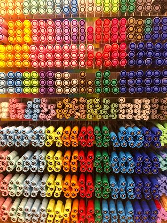 A lot of markers are on the shelf in the store. Color spectrum of markers.