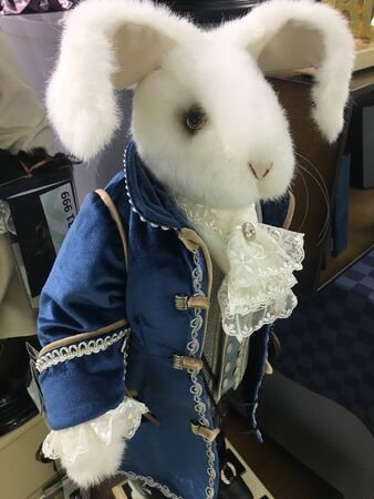 Fun close-up of stuffed Easter bunny on white. White toy rabbit in blue camisole