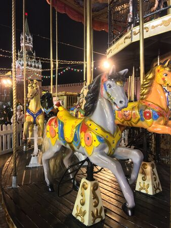 Festively decorated roundabout in Moscow. Carousel in Moscow. Carousel with horses