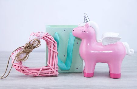 A pink unicorn stands next to a gift bag and a toy heart. Cute gift for a girl. Stockfoto