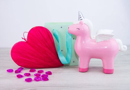 A toy Pegasus stands next to a large red heart. A gift for a woman.