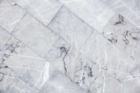 diagonal staggered design of white carrara marble flooring tiles used as kitchen countertop backsplash or wall and floor tiles