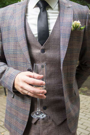A man in a three-piece suit holds a glass. To close. A mans hand holds a glass of white wine. The grooms suit Stockfoto