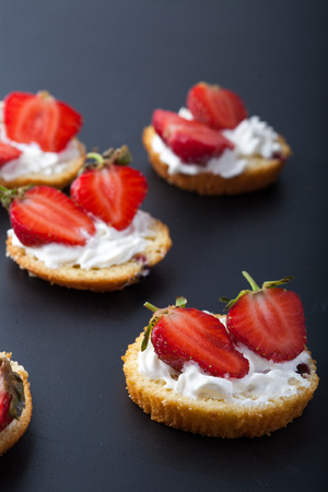 Fluffy buttermilk biscuits shortcake with red ripe strawberries and fresh whipped cream on a black background. Close up