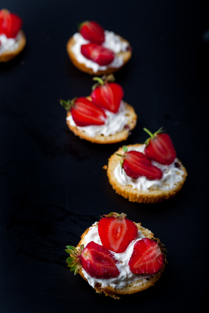 Fluffy buttermilk biscuits shortcake with red ripe strawberries and fresh whipped cream on a black background. Vertical image. Copy space