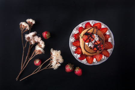 Homemade pancakes with strawberries, whipped cream and chocolate topping, decorated with flowers on black background. Overhead shot. Flat lay. Copy space.