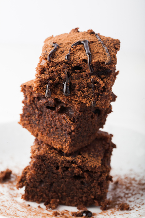 Stack of brownies on white wooden background. Chocolate cake close up. Copy space.