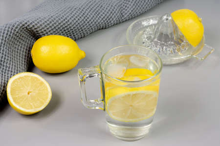 Cup of lemon water, lemon and lemon squeezer
