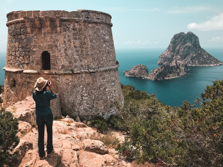 Islets of Es Vedra and Es Vedranell, Ibiza, Spain.Woman in the tower of Savinar Stock Photo