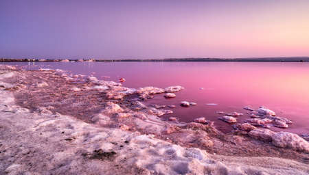 Beautiful and peaceful sunset landscape at the pink salt lake of Salinas de Torrevieja in Alicante, Spain, belonging to the Mata natural park