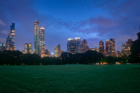 Manhattan skyscrapers viewed from the central park meadow at night with city lights
