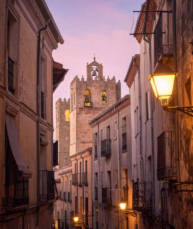 Historic architecture of the streets and tower of the Romanesque cathedral of the city of Siguenza, Guadalajara, Spain, at sunset