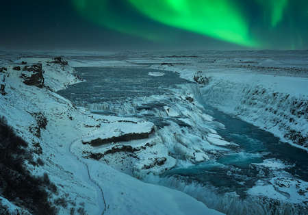 Snowy landscape at night at Gullfoss Falls with Northern Lights in Iceland during Christmas Standard-Bild