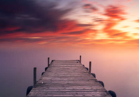 Relaxing and beautiful red Mediterranean sunset, on Albufera lake in Valencia, Spain on a jetty in front of silky water