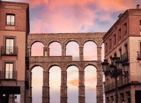 Aqueduct of Segovia and typical architecture in the historic center of the city, during a sunset of reddish and bluish tones Standard-Bild