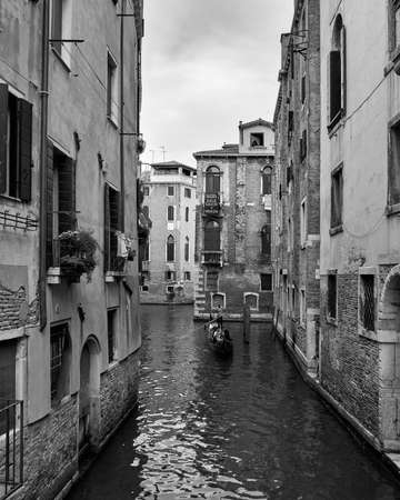 Venice, August 3, 2018. Black and white photograph of one of the city's streets and canals. Gondolier carrying tourists in his gondola