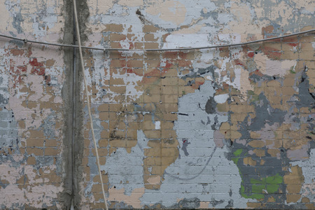 Old color brick wall with expressive spots of blue, beige, gray, lilac, green. Unreproducible picture. Renovation concept.