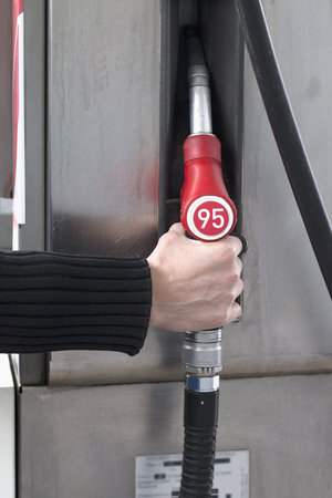 Male hand takes no fuel for a gas station. Expensive gasoline. Vertical