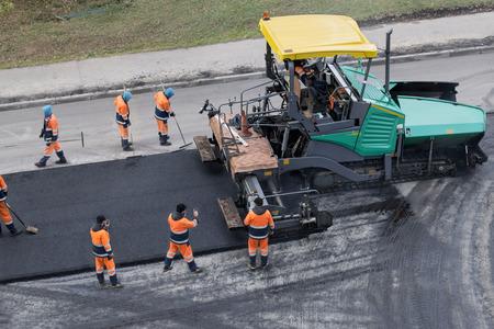 アスファルトの舗装機またはフィニッシャー。道路の更新プロセス、建設作業。コラージュ、認識できない労働者。高角度ビュー。