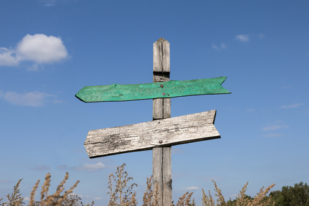 old wooden signpost with two arrows with copy space