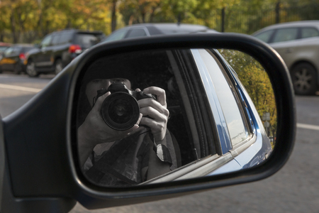 Hidden photographing from car window. Reflection in car mirror with hands. Paparazzi concept