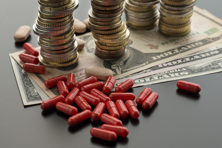 Red pills or capsules against dollar bills and stacks of coins on the dark background. Concept of costly treatment Stok Fotoğraf