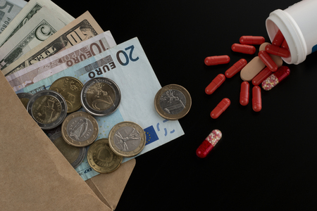 Euro and dollar currency in the envelope against scattered tablets, pills, capsules.  Medical expenses, purchase of medications