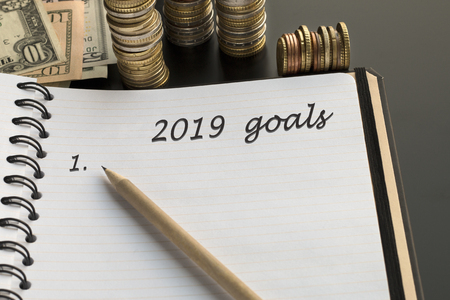 Notepad with 2019 goals text, pencil, money background. Topic of dreams, goals, plans