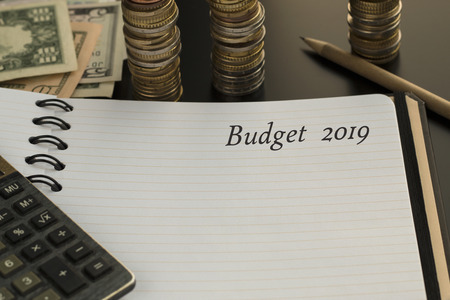 Budget planning concept. Notepad with Budget 2019 text, pencil, calculator and money background. Financial planning