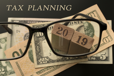 Tax planning concept. Glasses, tax planning 2019 text, dollar banknotes background