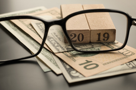 Glasses, number 2019 on the dollar banknotes background. Selective focus
