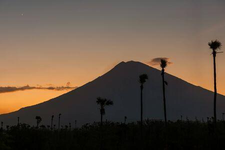 Orange sunset above Agung volcano, Bali island. Volcano view from black sand beach at dusk, Indonesia. 免版税图像