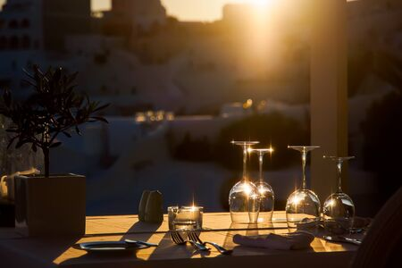 Table de restaurant décorée de verres sur terrasse à la lumière du coucher du soleil sur l'île de Santorin, Cyclades, Grèce