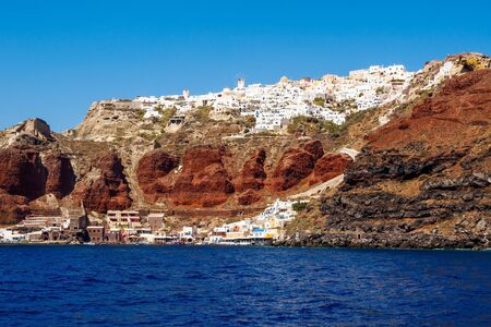 Amazing Santorini view on white cave houses from the Aegean sea. Santorini, Cyclades, Greece.