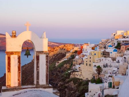 Church bell and Santorini island view on cave houses. Cyclades, Greece. Stok Fotoğraf - 148183165