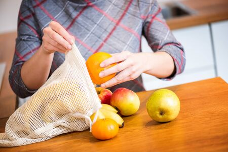 Eco packs. Woman hand getting out fruits after shopping from Eco bag. Anti-plastic bags. Zero Waste. 免版税图像