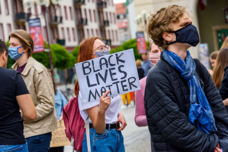 """Wroclaw, Poland, 06.06.2020 - Young people hold a poster with words """"Black lives matter"""" on polish peaceful protest against racism and hatred in Wroclaw city. Editorial"""
