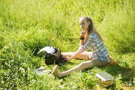 beautiful young blonde hair woman types on vintage typewriter at outdoor