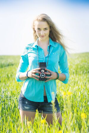 young blond hair woman with vintage camera on a summer green wheat field who feels inspiration and takes pictures